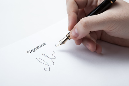 pen in the man's hand and signature on a white closeup Stock Photo - 27997176