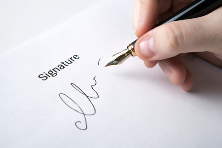 pen in the man's hand and signature on a white closeup Stock Photo - 27997294