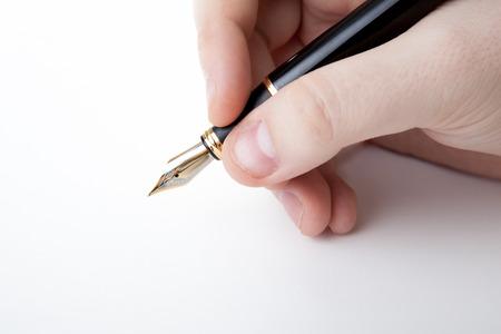 dispositions: pluma en la mano del hombre a la firma en un primer blanco Foto de archivo