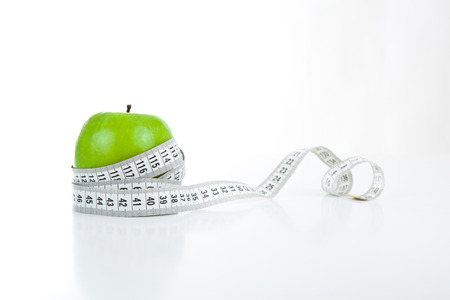 tapeline: green apple with a ruler on a white background Stock Photo