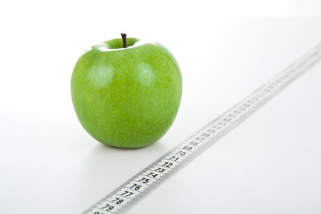 green apple with a ruler on a white background photo