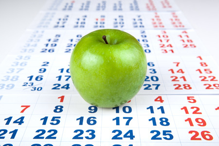 green apple on sheets of wall calendar closeup Stock Photo