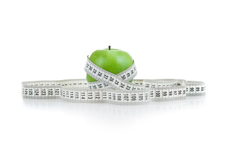 green apple with a ruler on a white background Stock Photo