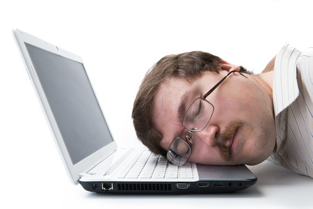 undergrad: man sleeping on a notebook keyboard at the workplace on a white  Stock Photo