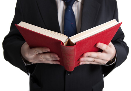 undergrad: man holding an open red book closeup on a white