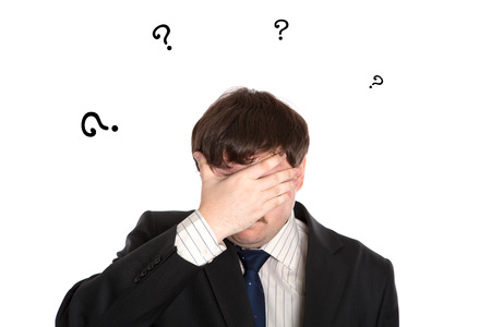 doldrums: businessman in stress with questions on a white background Stock Photo