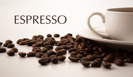 cup of black coffee and roasted coffe beans close-up with title espresso photo