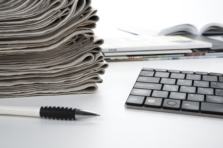 stack of newspapers and keyboard closeup on white