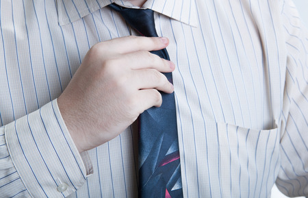 respectability: hand business man straightens his tie closeup Stock Photo