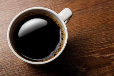 cup of black coffee on the oak desk photo