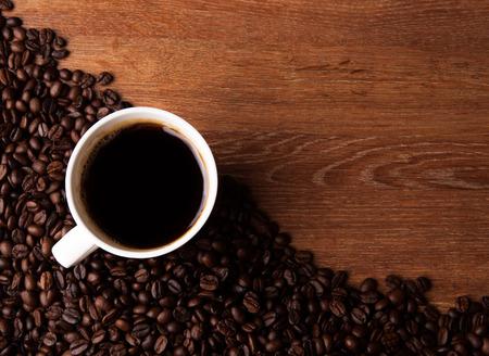 chicchi di caff�: tazza di caff� nero con chicchi di caff� arrostiti sulla scrivania di legno Archivio Fotografico