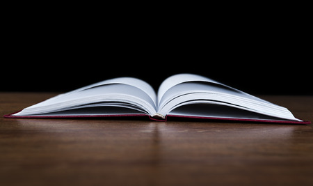 open up: open book on the wood table on a black background Stock Photo