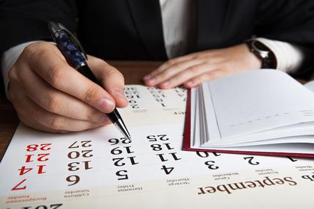 dispositions: hombre calcula los planes de futuro con el calendario de cerca Foto de archivo