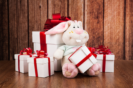 soft toy: white gift boxes and soft toy on a wood background