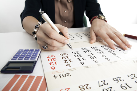 dispositions: woman calculates future plans with calendar close up