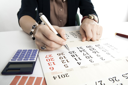 woman calculates future plans with calendar close up