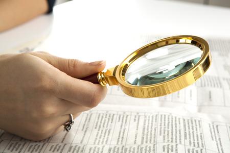 directorio telefonico: trabajador examina un texto lupa de cerca Foto de archivo
