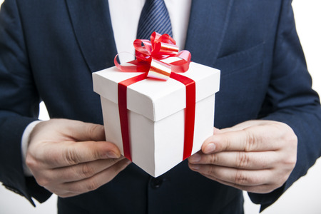 man gives gift box close up on a white photo
