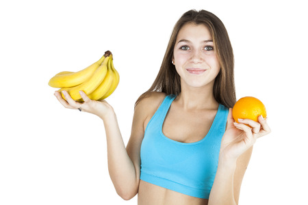 sober: Athletic girl holding fruit on a white background