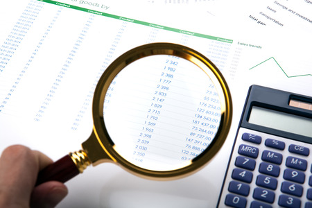 man considers the budget through a magnifying glass close up