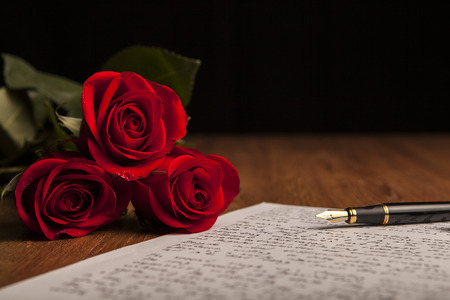 still life of a fountain pen, paper and flowers roses close up