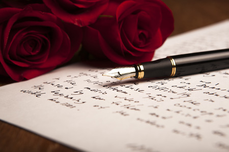 treatise: still life of a fountain pen, paper and flowers roses close up