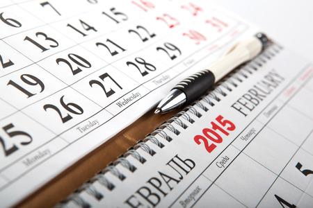dispositions: calendarios de pared con la pluma sentado en la mesa de cerca