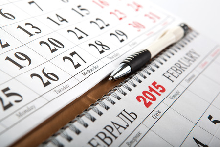 dispositions: wall calendars with pen laid on the table close up