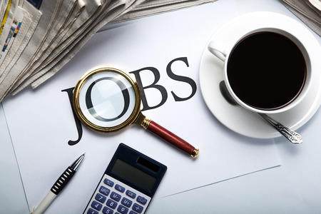 job vacancies: title jobs with loupe, pen, newspapers, cup of coffee and calculator