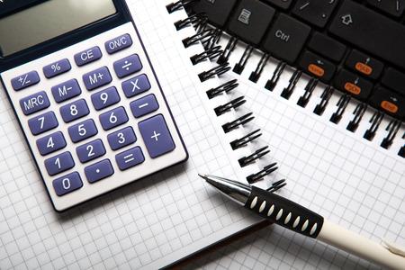 dispositions: pluma con la calculadora en un bloc de notas y el teclado de cerca