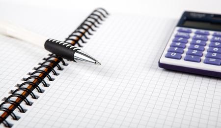 dispositions: pluma en un cuaderno en una celda y una calculadora de cerca