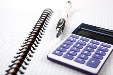calculadora: pluma en un cuaderno en una celda y una calculadora de cerca