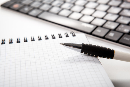 dispositions: pen on a notebook into a cell and keyboard close up