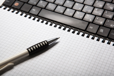 pen on a notebook into a cell and keyboard close up