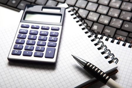 algebra calculator: pen with calculator on a notebook and keyboard close up
