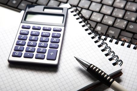 calculadora: pluma con la calculadora en un bloc de notas y el teclado de cerca