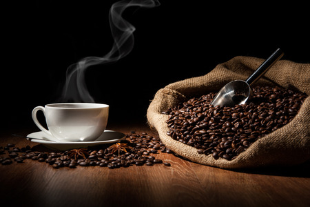 cup of coffee, coffee beans and bag on a wood table Stock Photo