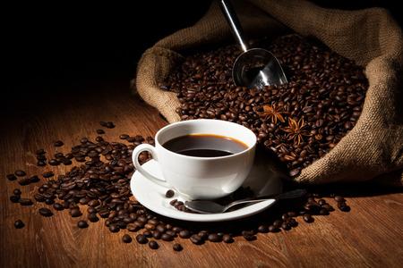 granos de cafe: taza de café, granos de café, la bolsa sobre una mesa de madera sobre un fondo negro