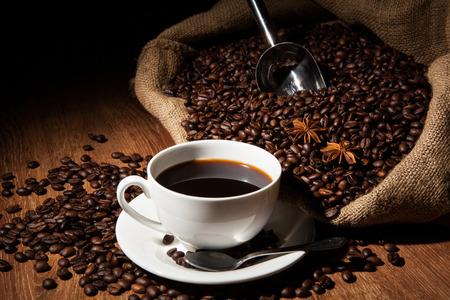 filiżanka kawy: filiżanka kawy, ziaren kawy, torebki na stole drewna