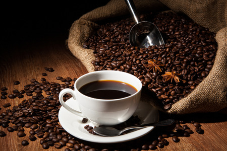 taza cafe: taza de café, granos de café, la bolsa sobre una mesa de madera