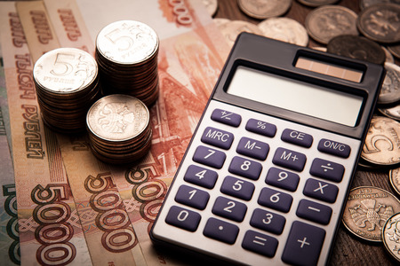 emolument: handful of Russian rubles with calculator close up