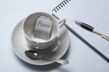 respite: business still-life with with a cup of tea and tea bags and notepad Stock Photo