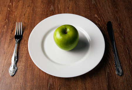 appointments: table appointments and the fresh green apple on a white plate close up Stock Photo