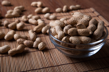 nosh: large grains of peanuts in the shell and the bowl close up