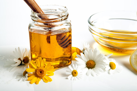 dulcet: Still life of honey, tableware, flowers, nuts, close up Stock Photo