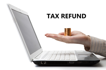 imposition: mans hand holding a stack of coins on a laptop with title tax refund