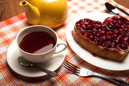 elegant party: Raspberry cake on a plate with a cup of black tea