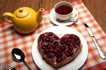 tea party: Raspberry cake on a plate with a cup of black tea