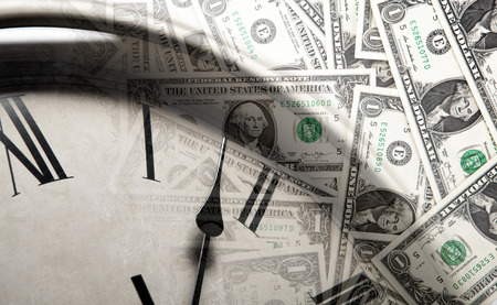 clock on the background of banknotes dollars close up Stock Photo