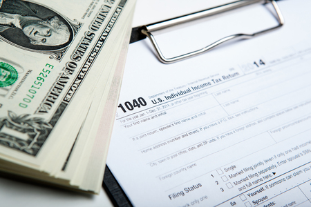 tax return: dollars and tax return work close up